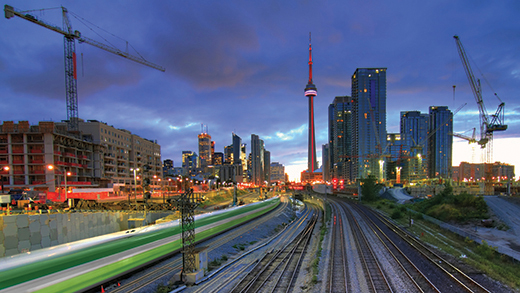 View of downtown Toronto skyline as seen at dusk from just east of the city on a GO train line.