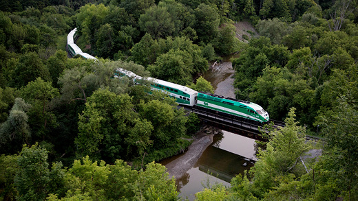 An aerial shot of a GO train crossing a tree banked river over a bridge.