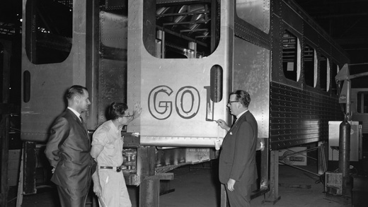 A black and white photo from the 60's featuring a train yard worker and 2 men in suits inspecting a train door with GO spray painted on it.