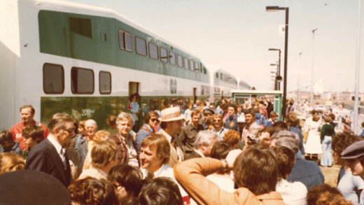 Shot from the early 80's of a crowd on a outdoor GO train platform. People are milling about and socializing in front of a double decker GO train.