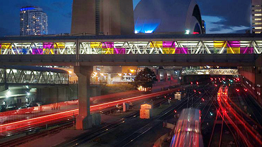 A night time shot of illuminated bridges and walkways crossing the rail corridor just west of Union Station.