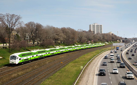 A GO train heading westbound on the Lakeshore line with cars driving along a busy Q.E.W.