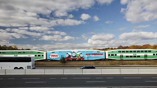 Photo of a GO Train travelling along with the highway with one car wrapped in an advertisement.