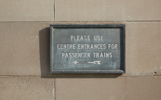 Closeup of an old sign on the wall of Union Station that reads 'Please use centre entrances for passenger trains.'