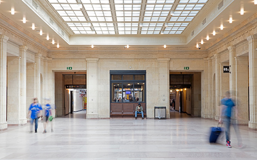 One of the west hallways at Union Station with three passengers walking through it while a fourth sits on a bench.