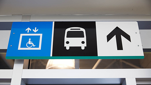 A sign above a doorway pointing in the direction of an Elevator and the Buses.
