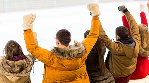 happy friends supporting team on ice rink arena