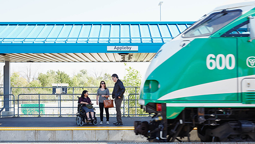 Three passengers, including a passenger using a wheelchair, chat on a train platform as a GO Train pulls into the station.