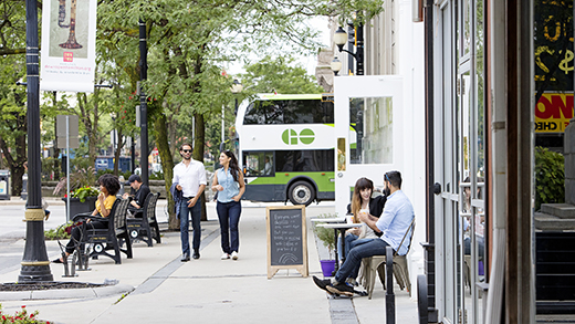 Photo of a couple walking down a sidewalk past a café with a GO Bus in the distance.