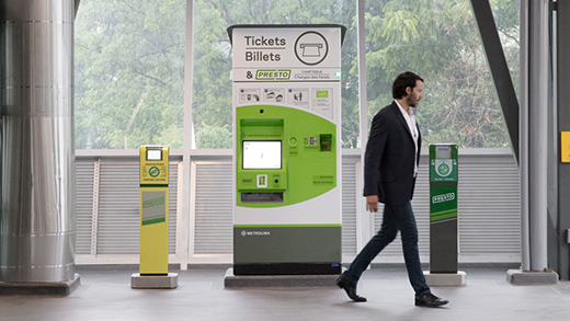 A passenger in a station walks past a ticketing machine and 2 Presto card machines.