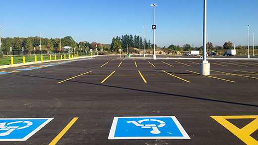 Photo of an empty parking lot of accessible and standard parking spots.