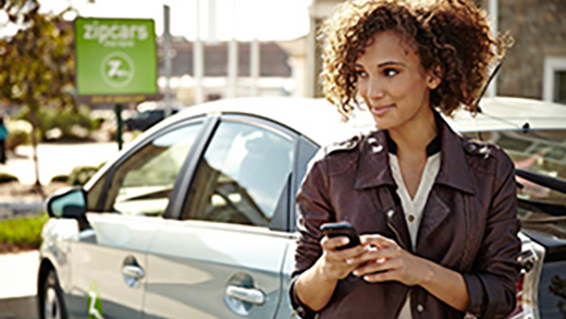 Photo of a woman standing next to a parked Zipcar.