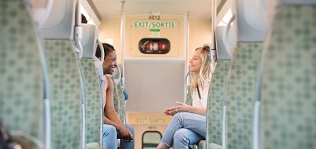 Two GO Train passengers on a train comfortably chat with each other across the aisle.