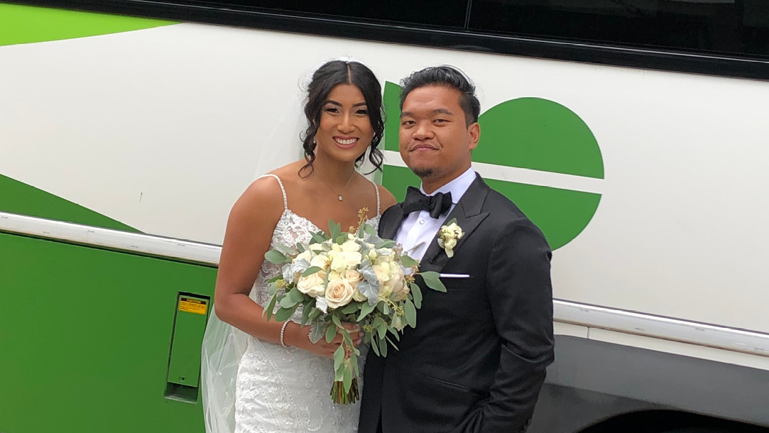 Nancy Moy and Drew Sison take wedding day photos in front of a GO Bus