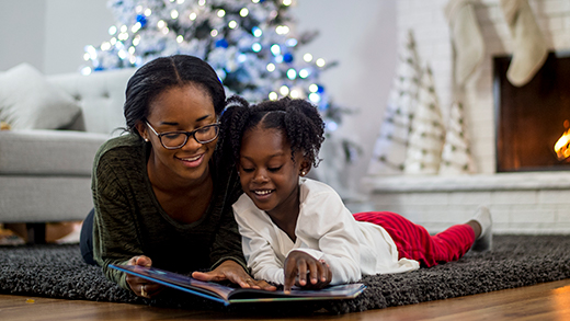 Two girls beneath a Christmas tree reading a book