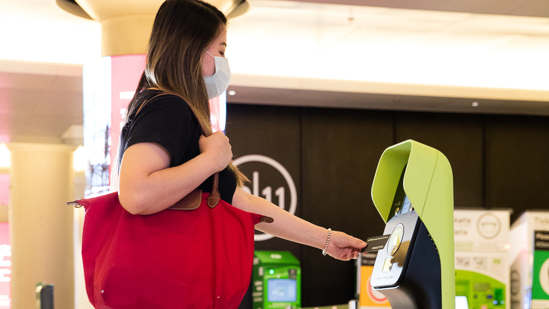 Woman tapping a new PRESTO device with PRESTO card at a GO Station