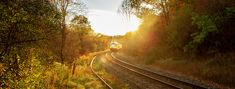 GO Train travelling on tracks as the sun is shining.
