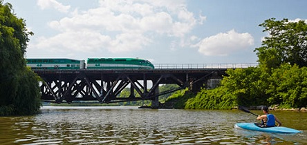 Person kayaking on the water as a GO Train passed by in the background