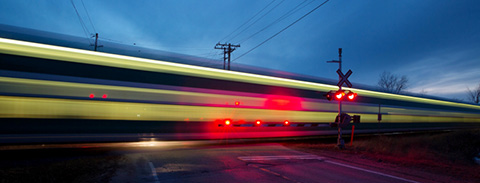Railway crossing at dusk with gates down and flashing lights as a speeding blur of a train passes through the intersection.
