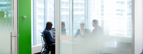 Four people meeting around a table in a small glass walled office space.
